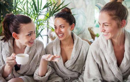 mujer: Tres mujeres j�venes felices que beben t� en el balneario
