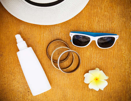 Sun flower: Fashionable clothes sunglasses, stylish bracelets, hat, cream for beach holiday. Top view. Summer vacation concept. Lizenzfreie Bilder