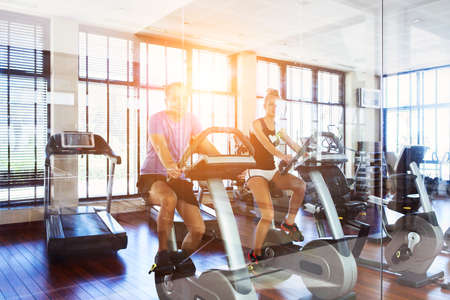 Healthy couple training on a treadmill in a sport center