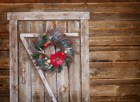 pomegranates: Christmas wreath on a rustic wooden front door Stock Photo