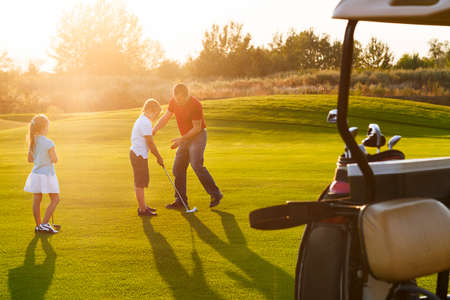 Casual kids at a golf field holding golf clubs studing with trainer. Sunset Stockfoto