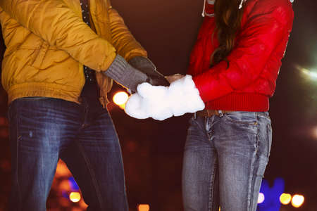 couple holding hands: Happy couple holding hands in knitted mittens. Close up Stock Photo