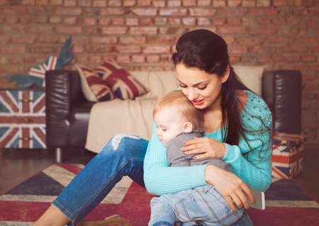 british girl: Young mother playing with her baby daughter at home