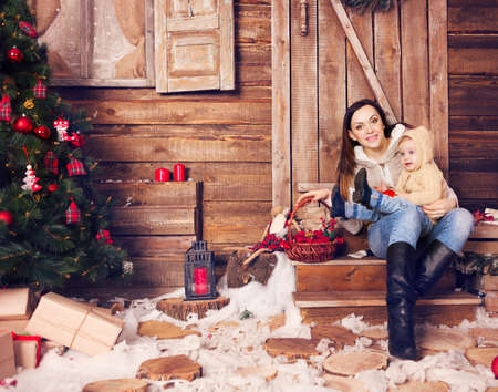 christmas time: Stylish motherand her child celebrating christmas in room over christmas tree. Happy family wearing trendy knitted sweaters