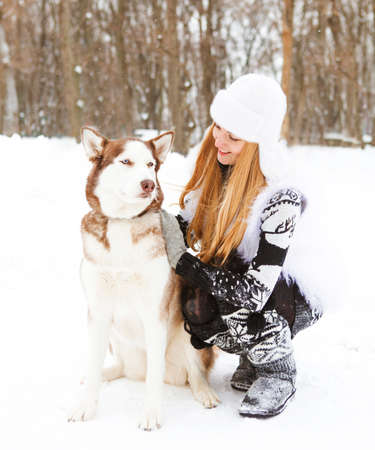 huskies: Happy young woman in the winter park with huskies dog