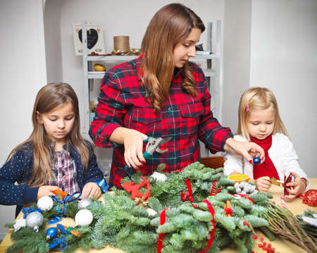advent wreath: Mother making an advent wreath with the kids - dressed for the christmas