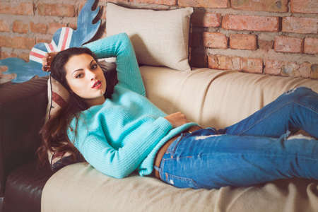 domiciles: Pretty brunette girl relaxing on the couch at home in the living room