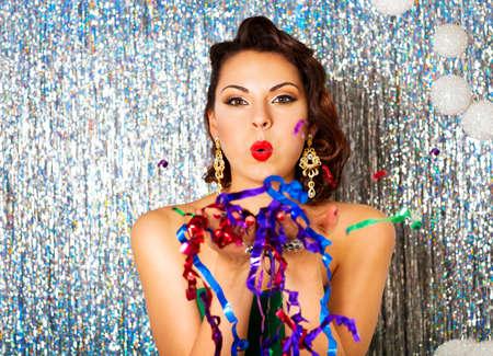 morena: Hermosa sexy joven morena con el pelo ondulado brillante noche componen labios rojos sosteniendo palmas con lentejuelas en frente de ella y les sopla un día de fiesta del Año Nuevo de Navidad de la diversión alegría