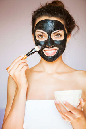 Young beautiful woman applying a mask for the face of the therapeutic black mud. Spa treatment