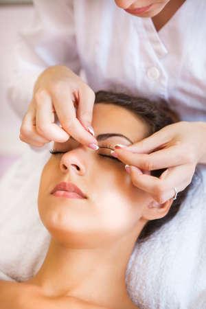 tweezing eyebrow: Beautiful young woman in cosmetic salon. Close up