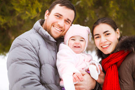 beautiful smile: Beautiful happy family wearing warm clothes in winter park
