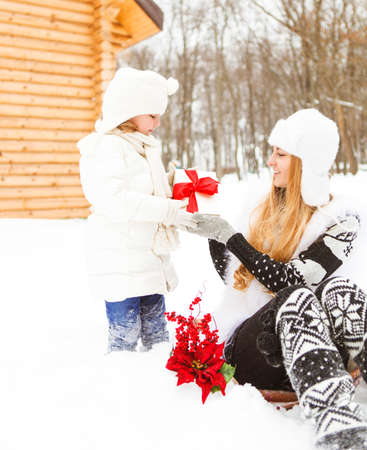 family outside: Happy young mother with daughter with present and christmas decorations