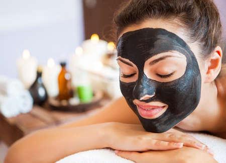 Junge schöne Frau in eine Maske für das Gesicht des therapeutischen schwarzen Schlamm. Spa-Behandlung Standard-Bild
