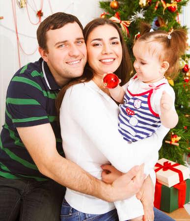 baby near christmas tree: Happy young family with Christmas baby near the Christmas tree