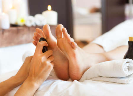 Massage of human feet by hot stones in spa salon. Close up