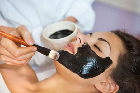Young beautiful woman in a mask for the face of the therapeutic black mud. Spa treatment Imagens