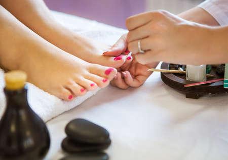 pedicura: Mujer en el salón del clavo que recibe pedicure por esteticista. Primer plano de la mano descansando sobre una toalla blanca femenina Foto de archivo