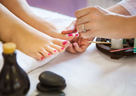 Woman in nail salon receiving pedicure by beautician. Close up of female hand resting on white towel