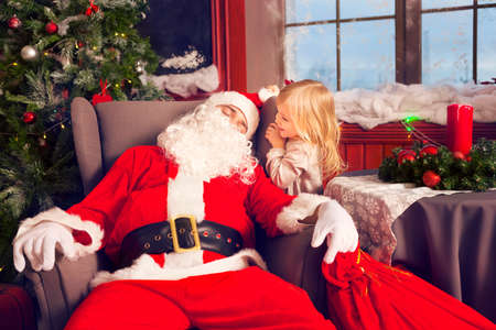 mail man: Photo of happy littlle smiling girl looking at sleeping Santa Claus with big bag of presents