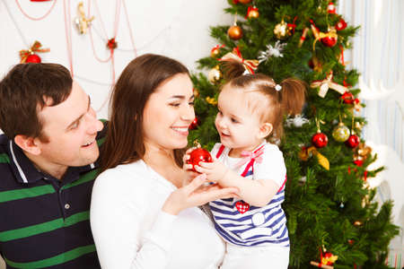 baby near christmas tree: Happy young family with Christmas baby near the Christmas tree