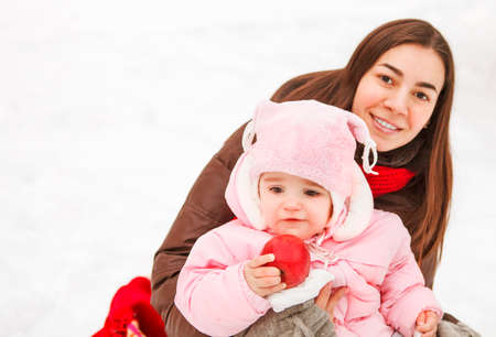 family with baby: Young brunette mother with her daughter outdoors. Winter