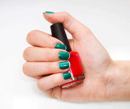 feminine beauty: Manicure. Beauty treatment photo of nice manicured woman fingernails holding red nail polish. Feminine nail art with nice glitter, green and white nail polish