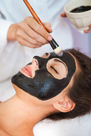 Young beautiful woman in a mask for the face of the therapeutic black mud. Spa treatment Stockfoto