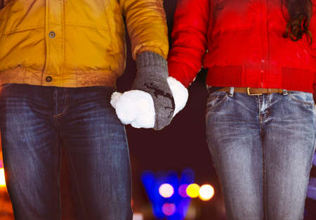 dating: Happy couple holding hands in knitted mittens. Close up Stock Photo