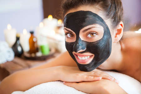 happy black woman: Young beautiful woman in a mask for the face of the therapeutic black mud. Spa treatment Stock Photo