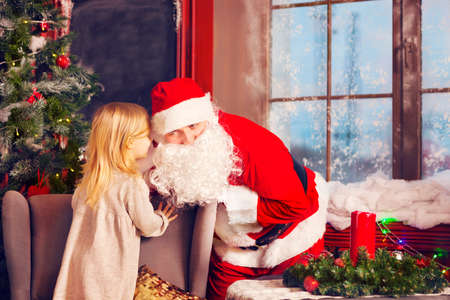 secret: Santa Claus and little girl. Christmas Scene. Girl telling her Christmas wish in Santa Claus near the Christmas Tree