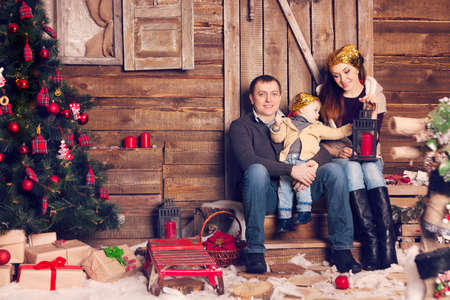 young tree: Stylish family celebrating christmas in room over christmas tree. Happy family wearing trendy knitted sweaters