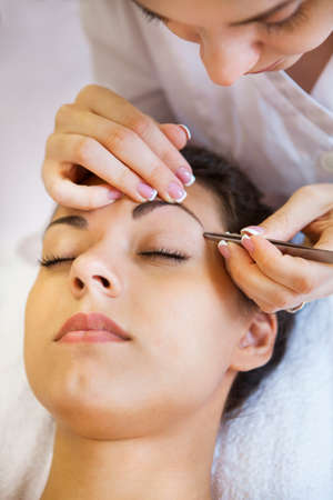 tweezing eyebrow: Portrait of a beautiful young woman in cosmetic salon. Close up. Beauty treatments
