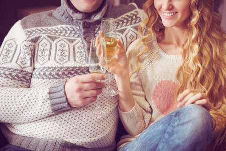 romantic evening with wine: Beautiful young couple celebrating christmas drinking champagne wine. Close up Stock Photo