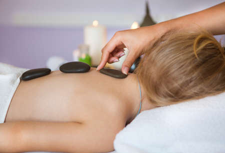 massieren: Nahaufnahme eines kleinen M�dchens zur�ck empfangen Massage mit hei�en Steinen