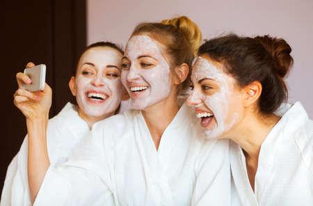 volti: Tre giovani donne felici con le maschere di protezione prendendo selfi in località termale. Frenship e benessere concetto