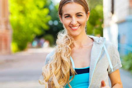 hoody: Young female runner in hoody is jogging in the city street