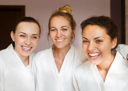 Three young happy women at spa resort. Frenship and wellbeing concept 스톡 콘텐츠