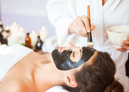 Young beautiful woman in a mask for the face of the therapeutic black mud. Spa treatment 스톡 콘텐츠