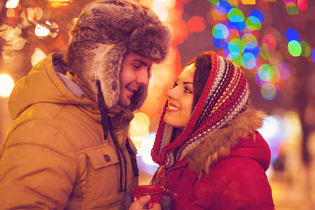 couple outdoor: Young happy couple in love outdoor in evening Christmas lights Stock Photo