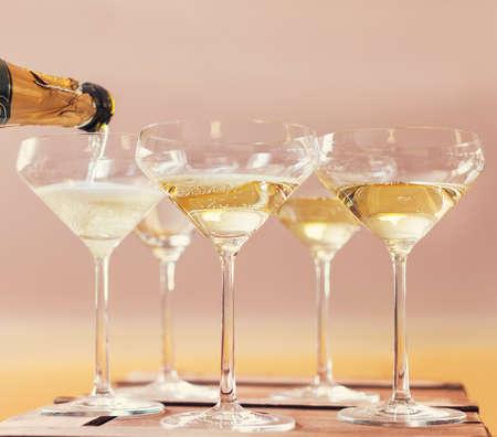 Champaign being pored into glasses. Retro toned image Standard-Bild