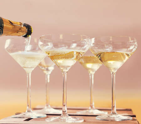 Champaign being pored into glasses. Retro toned image Stockfoto