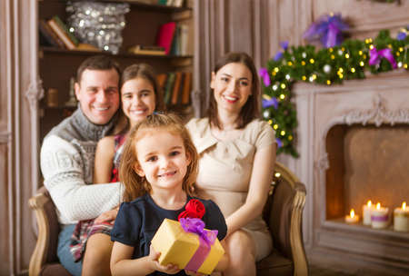 Stylish happy family celebrating christmas in room over christmas tree photo
