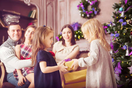 Stylish happy family celebrating christmas in room near the christmas tree photo