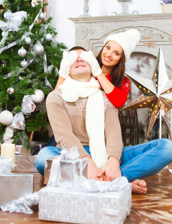 relaxing at home: Young happy smiling couple by the Christmas tree Stock Photo