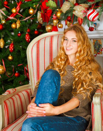 curved leg: Portrait of the happy young woman by the Christmas tree