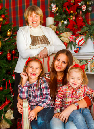 Portrait of a grandmother and teen granddaughters near the Christmas tree being happy and joyful photo