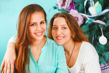 Portrait of a mother with teen daughter hugging at home near the Christmas tree being happy and joyful photo
