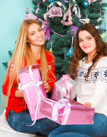 having fun in winter time: Two pretty best friends girls opening Christmas presents near the Christmas tree. Having fun together at winter holiday time