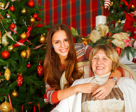 Portrait of a grandmother and teen granddaughter near the Christmas tree being happy and joyful photo