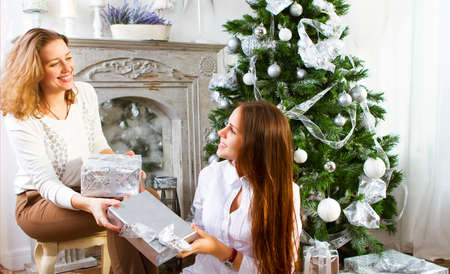 Portrait of a mother with teen daughter at home near the Christmas tree being happy and joyful photo
